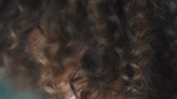 Cover Image for Curly Girl Turns and Looks at the Camera.  Portrait