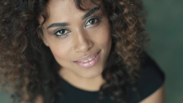Cover Image for Young Hispanic Woman with Curly Hair and Brown Eyes Smiling at the Camera