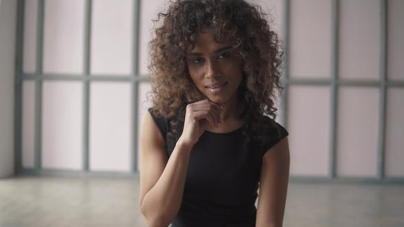 Cover Image for Portrait of a Beautiful Young Hispanic Woman in a Black Dress. Curly-haired Girl Cute Smiling and