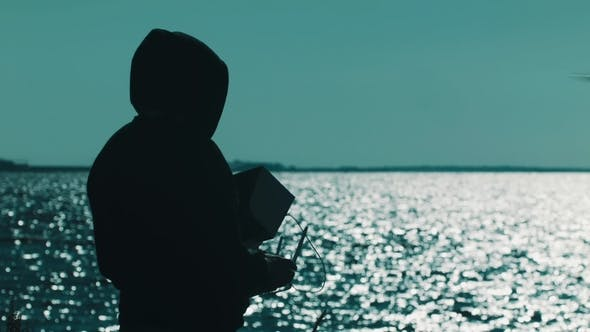 Thumbnail for Silhouette of Man in Hood Catching Flying Quadcopter on Lake Shore