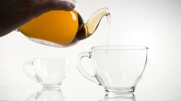 Thumbnail for Tee Gießen. Tee wird in Glas transparente Teetasse gegossen. Tee-Zeit. Transparente Glas-Teekanne und