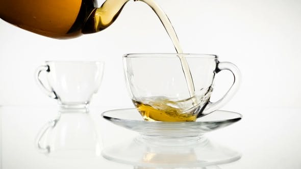 Thumbnail for Tea Pouring. Tea Being Poured Into Glass Transparent Tea Cup. Tea Time. Transparent Glass Teapot and