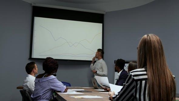 Thumbnail for Ein junger Mitarbeiter des Unternehmens in einem weißen Hemd berichtet über den Fortschritt der Arbeit im