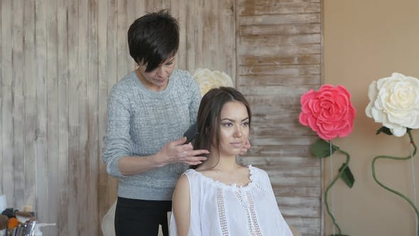 Thumbnail for Makeup Artist Stylist Works with Model. Hairdresser Does the Hair Styling of the Model. A Woman Is