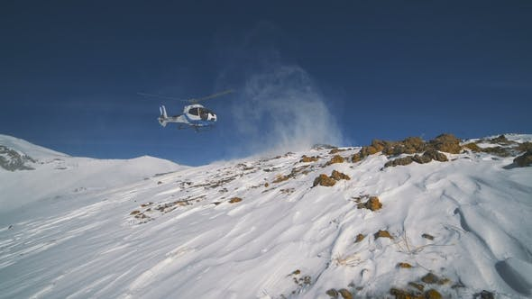 Thumbnail for The Heliskiing Helicopter Landed in the Mountains in Winter, Raising a Cloud of Snow