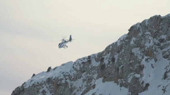 Cover Image for The Helicopter Flies Against the Background of a Rocky Snow-capped Mountain