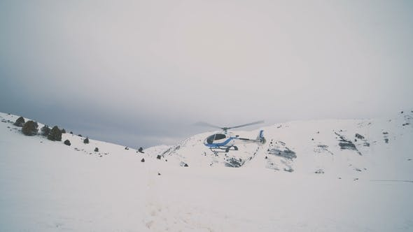 Cover Image for A White Helicopter at the Background Cloudy Sky is Landing in Snow Mountains