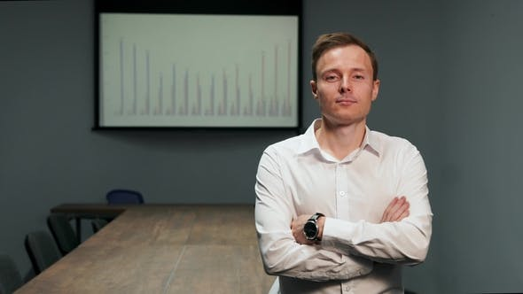 Cover Image for Man in a White Shirt Standing in the Office on the Background of the Conference Table