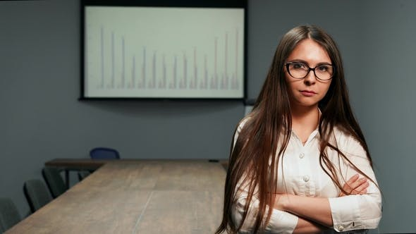 Cover Image for Beautiful Girl in Office Clothes Standing in Conference Room with Glasses