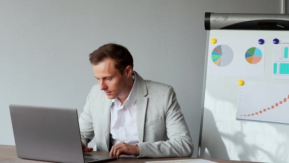 Thumbnail for European Male Sitting at a Laptop in the Office with a White Shirt
