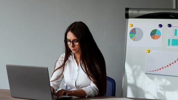 Cover Image for Beautiful European Girl Sitting at a Laptop in the Office with a White Shirt