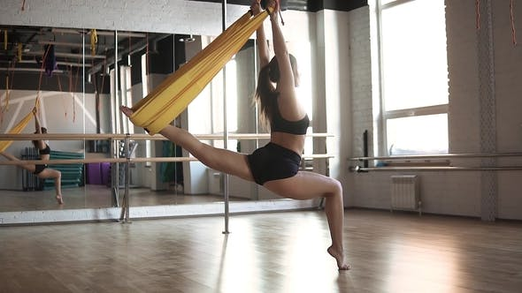 Antigravity Yoga. Sports Girl Engaged in Aeroyoga in the Gym