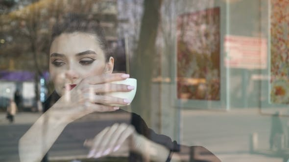 Thumbnail for Young Woman Looking Outside Through the Window in a Coffee Shop. She Looks Happy. We See Traffic and