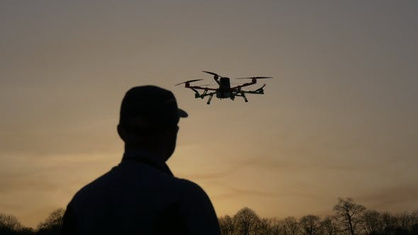 Thumbnail for Man Silhouette Drone Control at Sunset