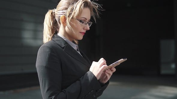 Thumbnail for the Girl in a Business Suit Sends a Texting on Mobile Phone. the Wind in Your Hair