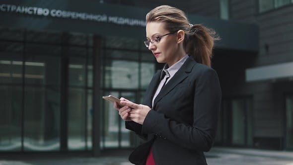 Thumbnail for Girl in a Business Suit Sends a Texting on Mobile Phone