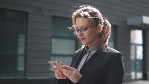 the Girl in a Business Suit Sends a Texting on Mobile Phone. the Wind in Your Hair