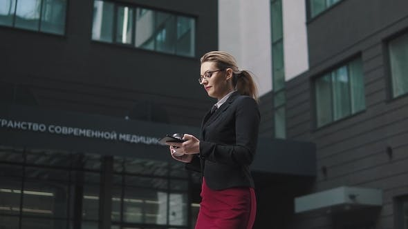 Thumbnail for Portrait of Business Woman with Mobile Phone Hands. the Girl in Business Clothes Is Walking Along