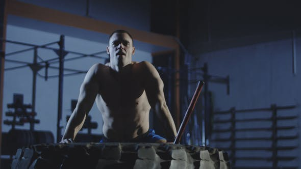 Tired Man Working Out with Sledgehammer