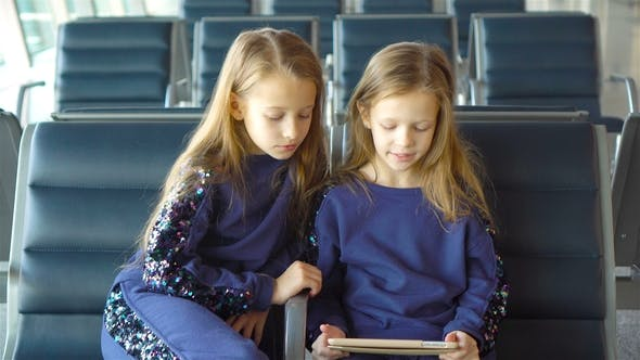 Thumbnail for Little Adorable Girls in Airport Waiting for Boarding Playing with Laptop