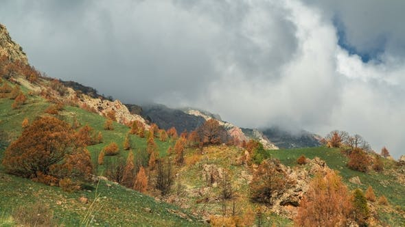 Thumbnail for Mountain Ridge with Thick Clouds, Covered with Fresh Green Grass and Trees with Orange Leaves in