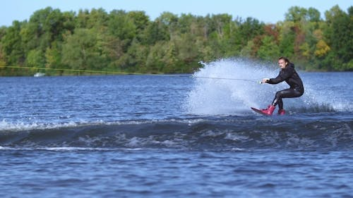 Wakeboarder Jumping High Above Water. Rider Wakeboarding