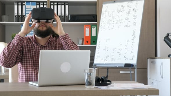 Cover Image for Bearded Man in an Office Takes VR Virtual Reality Headset From the Desk and Puts It on His Head