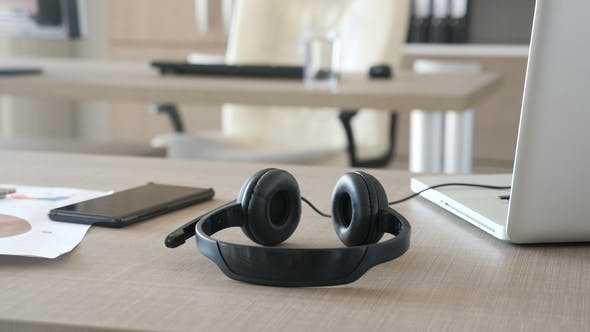 Thumbnail for Customer Care Headset on a Table Next To a Laptop and Smartphone