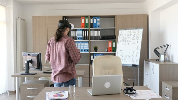 Thumbnail for Bearded Man in Casual Clothes in an Office Puts a Virtual Reality Headset on