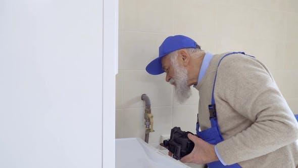 Thumbnail for Senior Gray-haired Man Wearing Coveralls Repairs Boiler