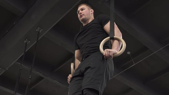 Thumbnail for Male Athlete Doing Rings Muscle Ups Exercise in Gym