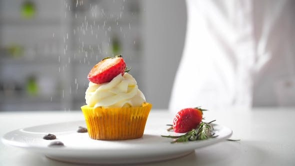 Thumbnail for Dessert Cook Female Hand Decorates Tasty Cupcakes White Cream Topping with Cutted Strawberry Pieces