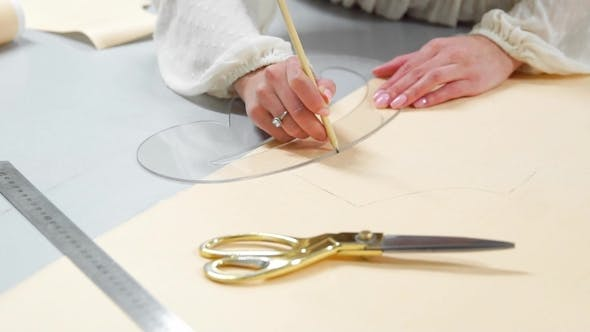 Female Fashion Designer Drawing Sketches for Clothes in Atelier