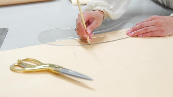 Cover Image for Young Female Designer with Tape-line on Her Neck Standing in Dressmaking Studio