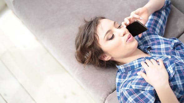 Thumbnail for Girl Lying on a Couch and Talking on the Phone