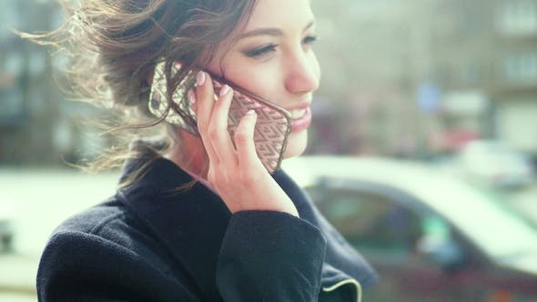 Cover Image for Attractive Happy Girl Talking on the Phone on the Street
