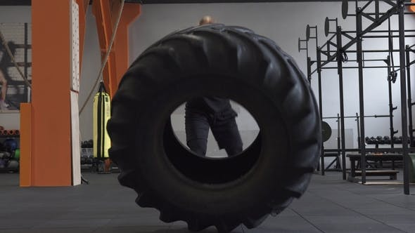Thumbnail for Fitness Man Doing Big Tire Flips Exercise in Gym