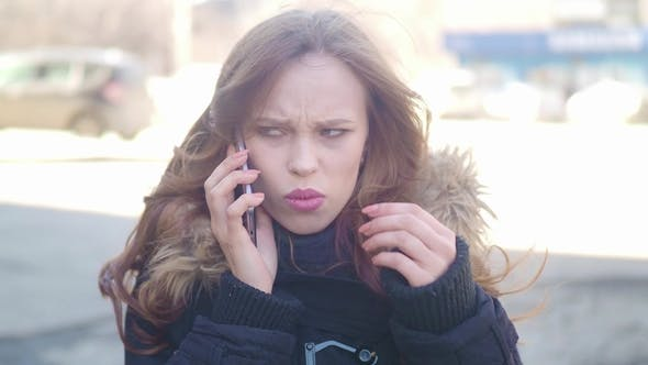 Thumbnail for the Girl on the Street Talking on the Phone. Quarrels and Gets Upset