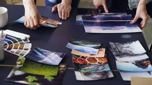 Tilt-up Shot of Women's Hands Placing Photos on Table in Modern Office