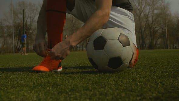 Thumbnail for Soccer Player Tying Shoelace on Football Pitch