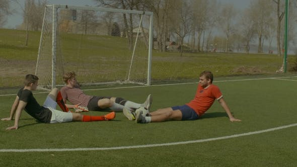 Footballers Relaxing on Soccer Field After Game