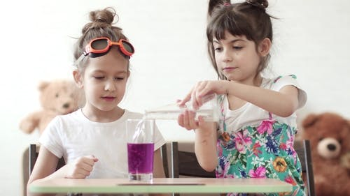 Children's Science. Children Conduct a Chemical Experiment at Home. Mixing of Iodine and Hydrogen