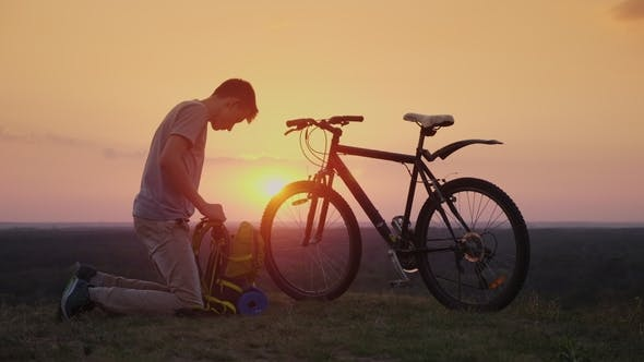 Thumbnail for A Young Man Puts Things in a Backpack. Sits By the Bike at Sunset