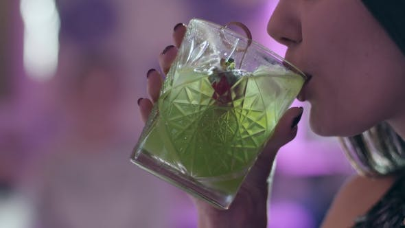 Thumbnail for Woman with Sexy Lips Drinks Green Cocktail in a Transparent Glass at Night