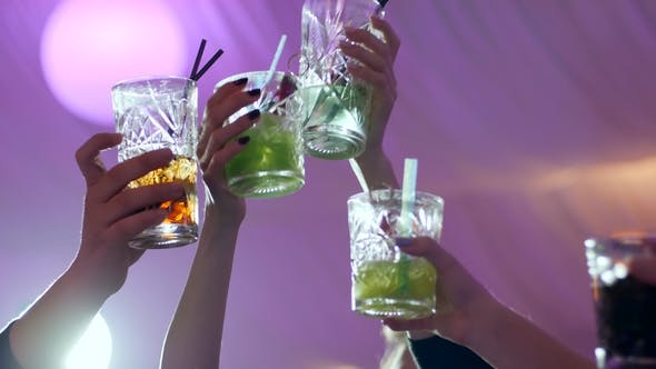 Friends Make Toast with Colorful Alcohol Cocktails and Straws in Nightclub on Background of Lights