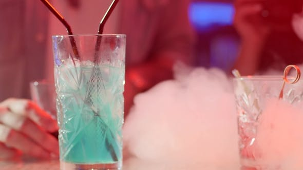 Thumbnail for Table with Colorful Beverages in Smoke on Background of Colored Lamps at Night