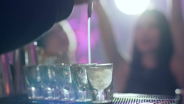 Thumbnail for Barman Pours an Alcoholic Cocktail into Small Glasses at Bar Counter
