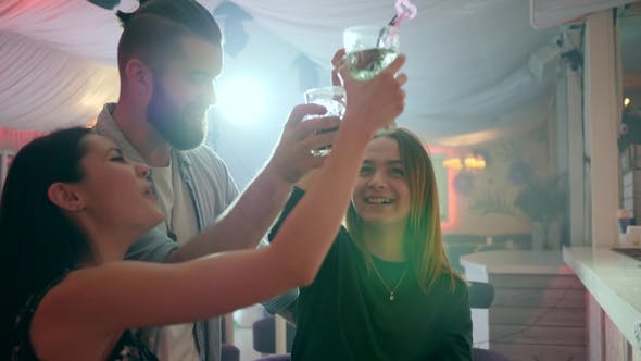 Thumbnail for Two Girls and One Guy Have Fun in a Club and Make a Toast with Glasses in Their Hands