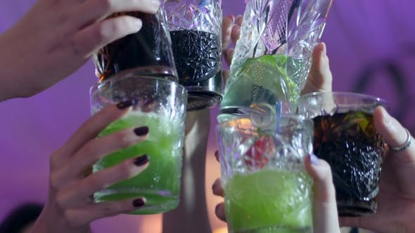 Thumbnail for People's Hands Make Toast with Glasses with Alcoholic Multi-colored Cocktails at Club