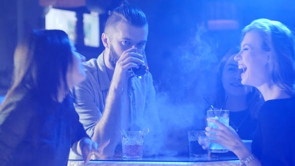 Thumbnail for Young Friends Having Fun at Table with Colorful Beverages in Smoke on Background of Colored Lamps